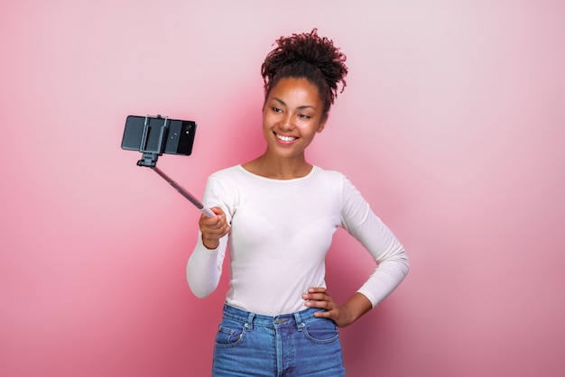 Young mulatto girl holding mobile phone takes a picture selfie