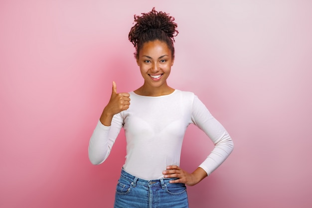 Young mulatto happy woman standing with thumbs up