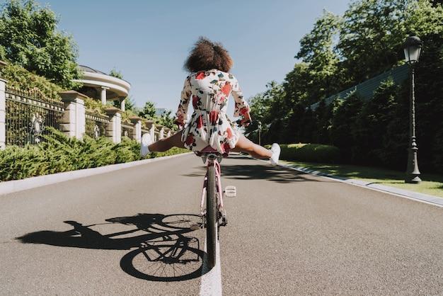 フラワードレスの若いムラートは外サイクリングです。