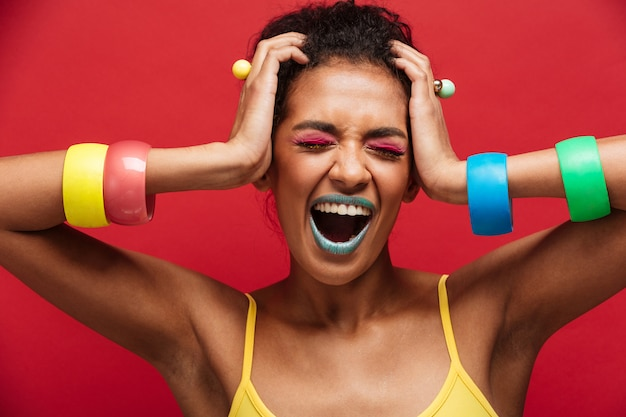 Young mulatto woman in colorful accessories being stylish grabbing her head and screaming with closed eyes, over red wall