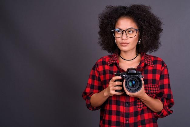 灰色の壁にアフロの髪を持つ若い多民族アフリカ系アメリカ人の流行に敏感な女性