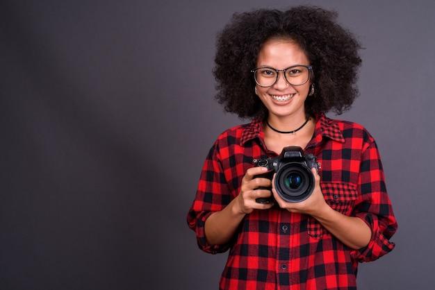 회색 벽에 아프로 머리를 가진 젊은 다중 민족적인 아프리카 계 미국인 hipster 여자