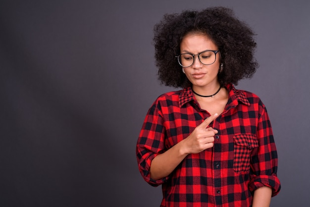 Young multi ethnic african american hipster woman with afro hair against gray wall