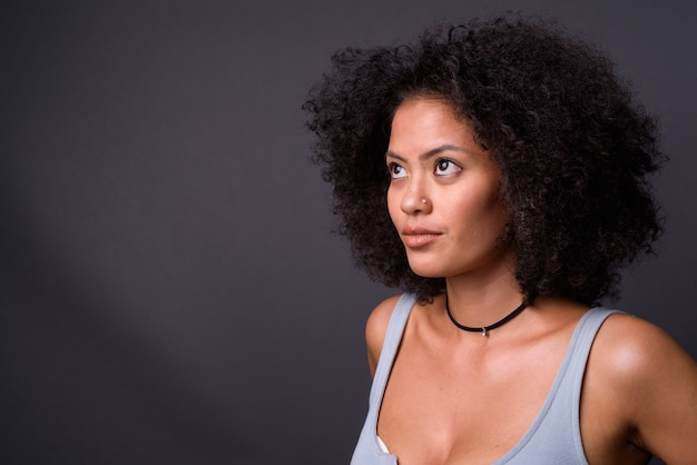 Young multi ethnic african american woman with afro hair against gray wall
