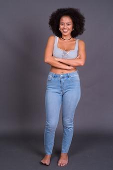 회색 벽에 아프로 머리를 가진 젊은 다중 민족적인 아프리카 계 미국인 여자