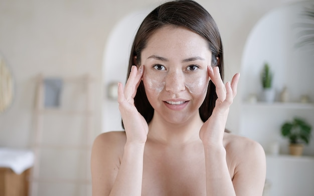 Young multi ethnic asian girl touching face with fingers apply caring about skin uses moisturiser creame morning routine grooming personal care skincare beauty treatment bodycare cosmetics concept
