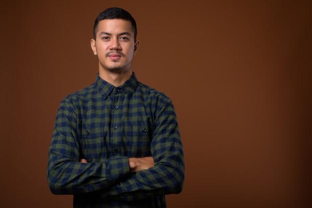 Молодой многоэтнический азиатский мужчина против коричневой стены