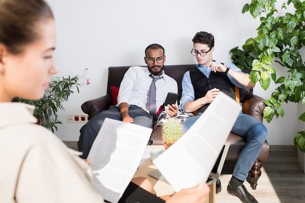 Молодые многоэтнические бизнесмены смотрят видео по телефону