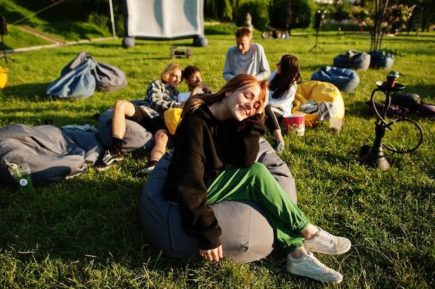 Молодые многоэтнические группы людей смотрят фильм на пуф в кинотеатре под открытым небом. закройте вверх по портрету смешной девушки.