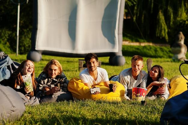 Молодые многоэтнические группы людей смотрят фильм на пуф в кинотеатре под открытым небом.