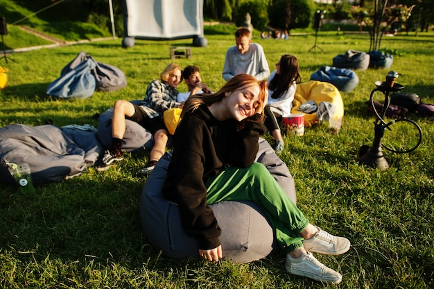Young multi ethnic group of people watching movie at poof in open air cinema. close up portrait of funny girl.