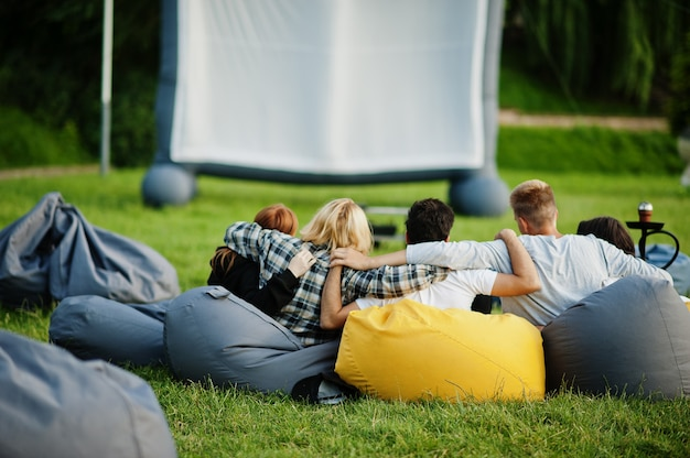 Young multi ethnic group of people watching movie at poof in open air cinema.