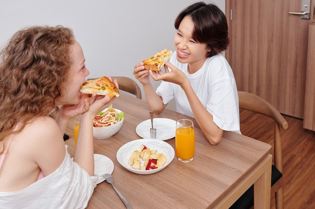 Young multi-ethnic lesbian couple eating pizza for dinner at home
