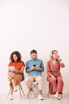 Молодой многонациональный мужчина и женщина взаимодействуют в социальных сетях с помощью гаджетов, пока позитивная девушка слушает музыку в наушниках