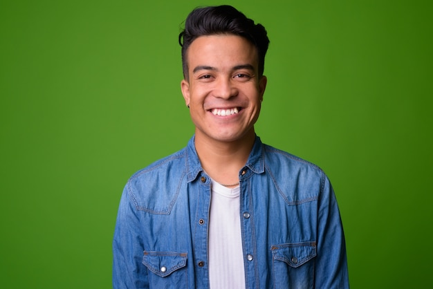 Young multi-ethnic man wearing smart clothing against green background