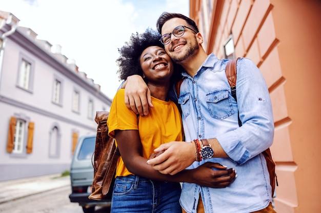 Молодая мультикультурная пара гуляет по улице, обнимается и наслаждается прекрасным днем.