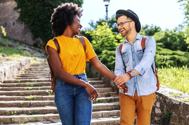 Молодые многокультурные счастливая пара, взявшись за руки во время прогулки по лестнице.