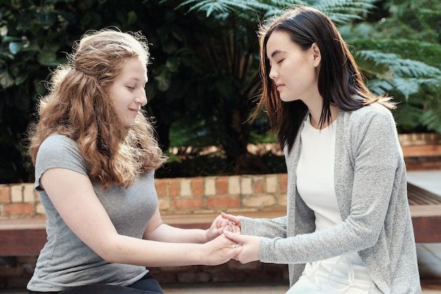若い多文化女性が祈りながら手を携えて