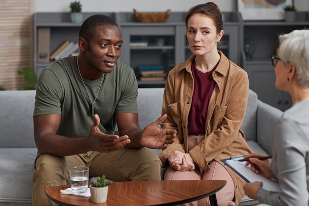 若い多民族のカップルは、オフィスのソファに座っている間、心理学者と相談します