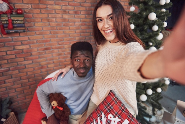 Young multiethnic couple meeting christmas hugging home. new year. festive mood of a man and a woman