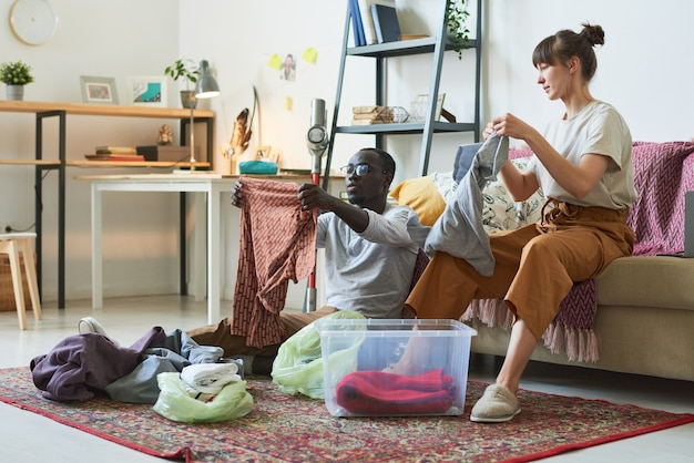 床に座って、自宅の箱に服を整理する若い多民族のカップル