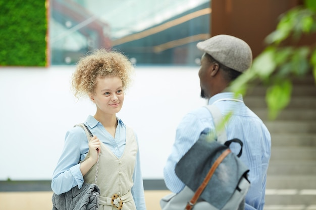 Young multiethnic couple talking to each other while standing at office building