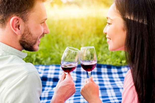 Young multiethnic enamored couple drinking red wine on picnic