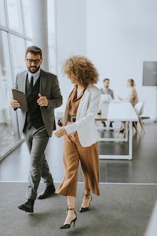 Молодые многонациональные предприниматели гуляют и разговаривают в современном офисе