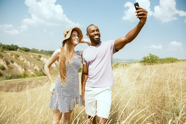 Young multiethnic international couple outdoors at the meadow in sunny summer day. african-american man and caucasian woman having picnic together. concept of relationship, summertime. making selfie.
