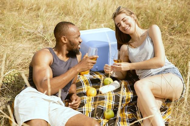 Молодая многонациональная международная романтическая пара на открытом воздухе на лугу в солнечный летний день. афро-американский мужчина и кавказская женщина вместе пикник. концепция отношений, лето.