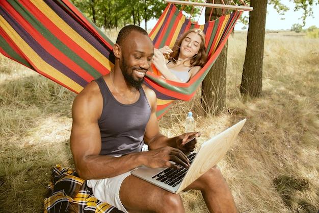 晴れた夏の日の牧草地で屋外で若い多民族の国際的なロマンチックなカップル。一緒にピクニックをしているアフリカ系アメリカ人の男性と白人女性。関係の概念、夏。