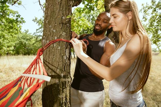 晴れた夏の日の牧草地で屋外で若い多民族の国際的なロマンチックなカップル。一緒にピクニックをする準備をしているアフリカ系アメリカ人の男性と白人女性。関係の概念、夏。