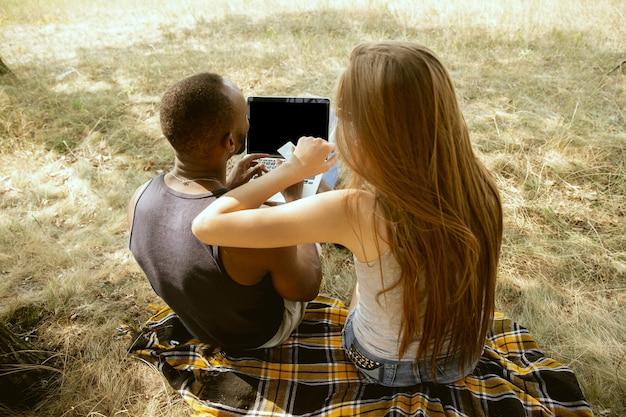 晴れた夏の日の牧草地で屋外で若い多民族の国際的なロマンチックなカップル。一緒に映画を見ているアフリカ系アメリカ人の男性と白人女性。関係の概念、夏。