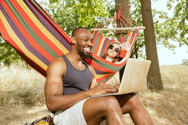 Young multiethnic international romantic couple outdoors at the meadow in sunny summer day. african-american man and caucasian woman having picnic together. concept of relationship, summertime. Free Photo