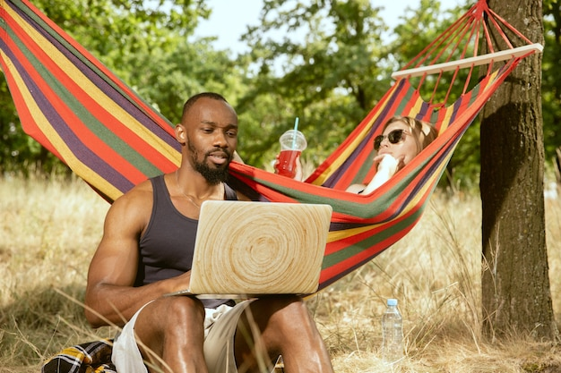 Young multiethnic international romantic couple outdoors at the meadow in sunny summer day. african-american man and caucasian woman having picnic together. concept of relationship, summertime.