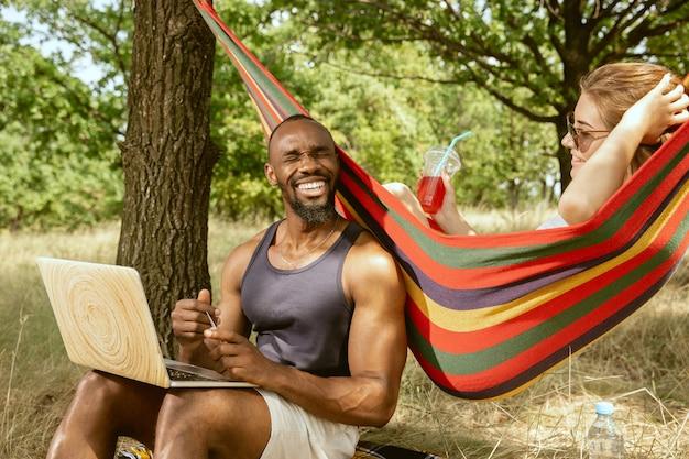 Giovani coppie romantiche internazionali multietniche all'aperto al prato nella soleggiata giornata estiva. uomo afro-americano e donna caucasica che hanno picnic insieme. concetto di relazione, estate.