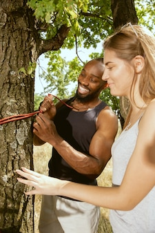 Young multiethnic international romantic couple outdoors at the meadow in sunny summer day. african-american man and caucasian woman preparing to picnic together. concept of relationship, summertime. Free Photo