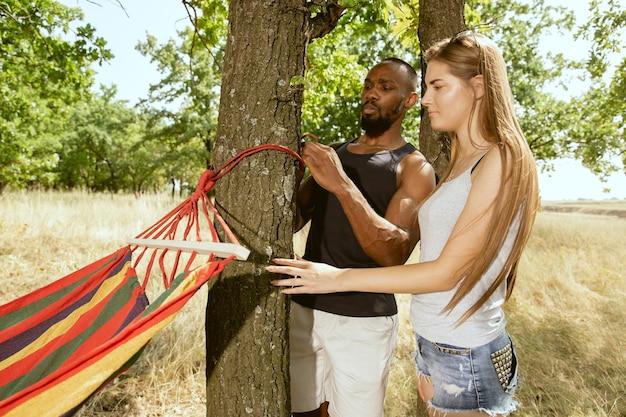Giovani coppie romantiche internazionali multietniche all'aperto al prato nella soleggiata giornata estiva. uomo afro-americano e donna caucasica che si preparano al picnic insieme. concetto di relazione, estate.