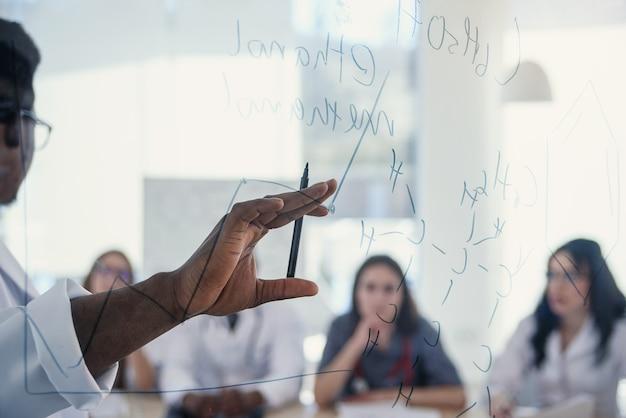 Молодые многонациональные интерны слушают лекцию афроамериканского доктора на медицинской конференции в клинике