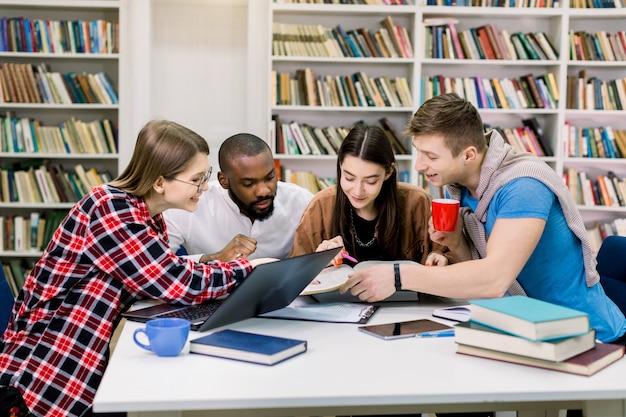 図書館で一緒に勉強している若い多民族大学生は、笑顔で本を見て、試験に役立つ新しい情報を見つけています。