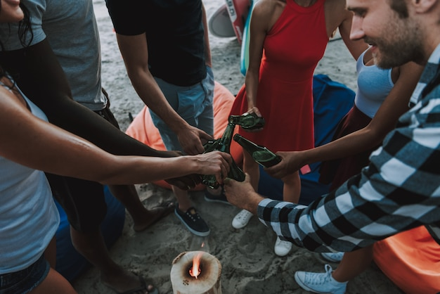 Young multinational company drink beer on beach.