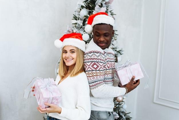 サンタの帽子をかぶった若い多国籍カップルは、クリスマスツリーの背景に贈り物を持って、カメラを見ながら微笑んでいます。クリスマスと新年のコンセプト。