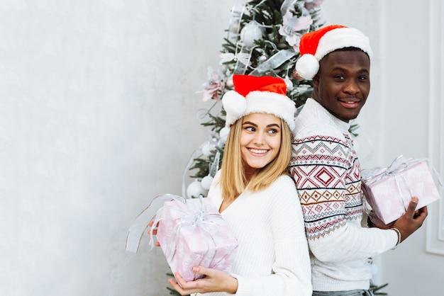 サンタの帽子をかぶった若い多国籍カップルは、クリスマスツリーの背景に贈り物を持って、カメラを見ながら微笑んでいます。クリスマスと新年のコンセプト