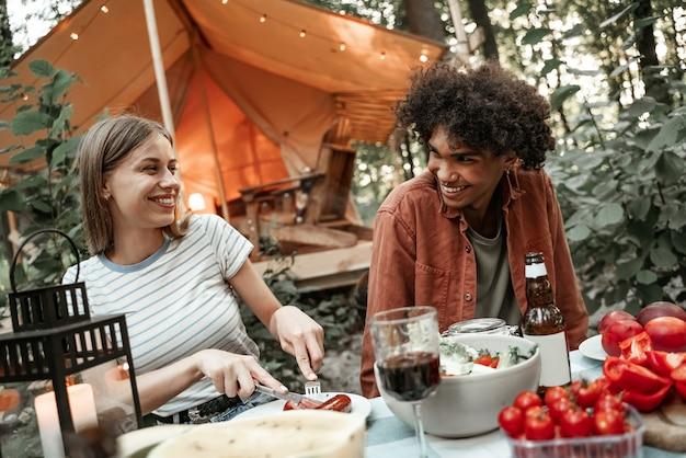 日没後に笑いながら、グランピングで夕食をとる若い多民族のカップル。電球のライトの下で野外ピクニックでキャンプする幸せなミレニアル世代。アウトドアで友達と過ごす時間、バーベキューパーティー