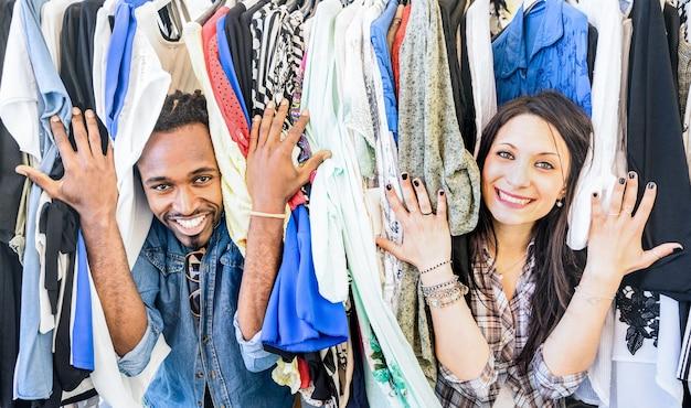 衣料品のフリーマーケットで楽しんでいる若い多民族のカップル-安いセールで時間を共有する親友-日常生活の瞬間を楽しむ愛好家-幸せな人々とのワードローブファッションショップのコンセプト