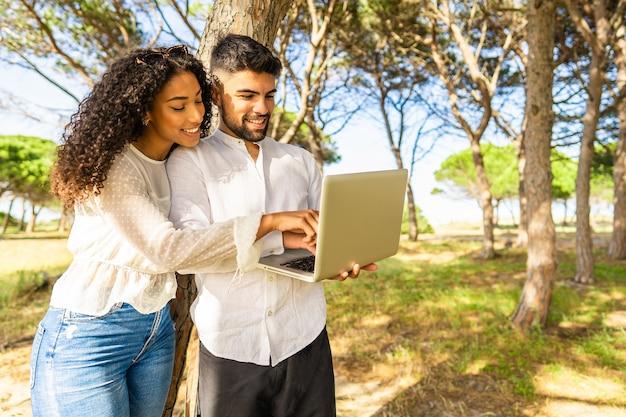 ラップトップを使用して海の近くのオーシャンリゾートの松林に立って休暇でテクノロジーを楽しんでいる若い多民族のカップル。自然の中でコンピューターの画面を指しているアフリカ系アメリカ人の黒人の女の子