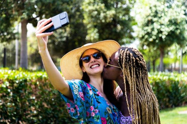 젊은 다인종 게이 여성 커플은 공원 lgbt 휴가에서 셀카를 찍고 뺨에 키스를 한다