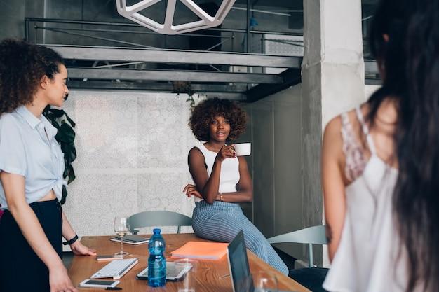 共同作業オフィスで非公式の会合を持つ若い多民族フリーランサーの女性