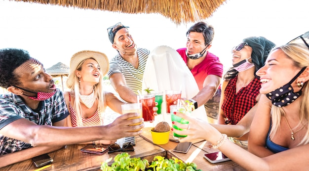 Young multiracial friends drinking at beach cocktail pub with open face mask