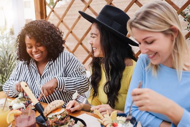 レストランで屋外で朝食をとっている若い多民族の友人-アジアの女の子の顔に焦点を当てる